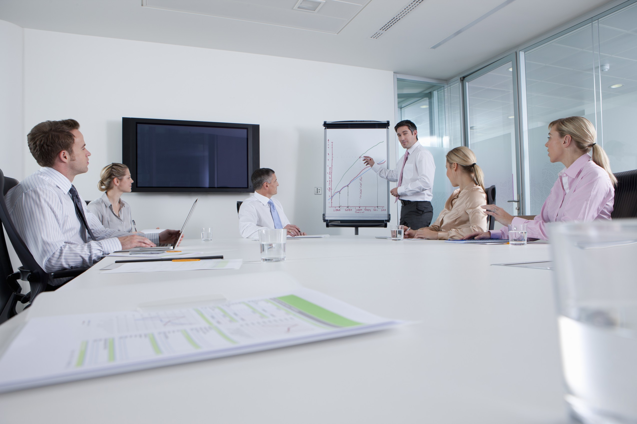 Businessman standing at chart and leading meeting in conference room